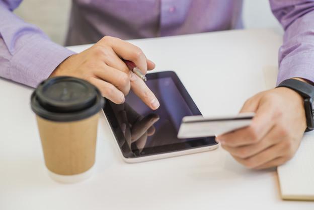 hombre-que-sostiene-tarjeta-credito-tableta-fondo-lugar-trabajo_1391-143